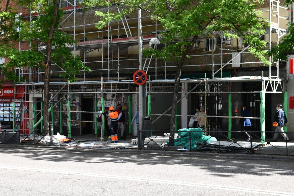 Imagen de un andamio con paso en la calle y coquillas de protección.